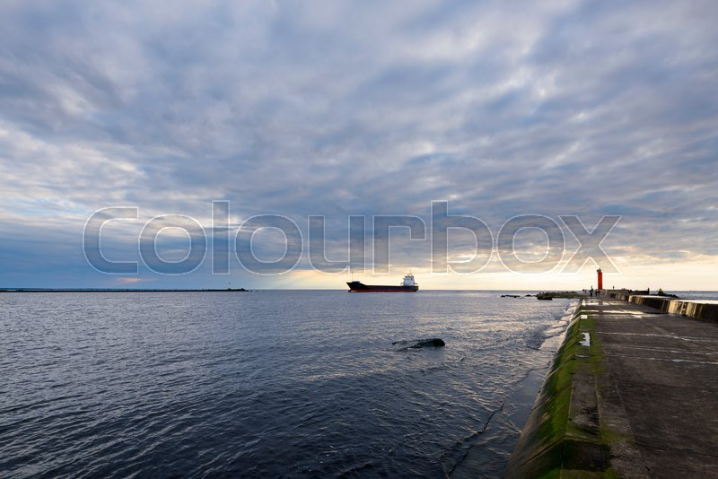 Stock image of 'lighthouse, pier, the gulf and cargo ship on a background at sunset'