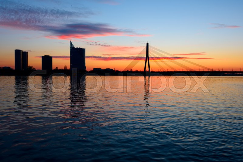 Stock image of 'Sunset on the town river with bridge in Riga, Latvia'