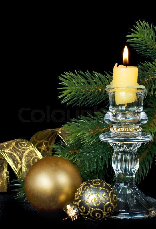 Stock image of 'Christmas composition with a burning candle on a black background'