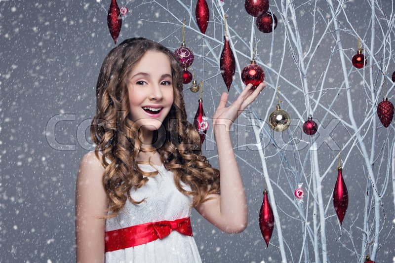 Stock image of 'Beautiful teen girl with long curly hair in white dress with red ribbon belt standing near white tree branches wiht christmas decorations hanging on it. Studio shot on grey background. Copy space.'