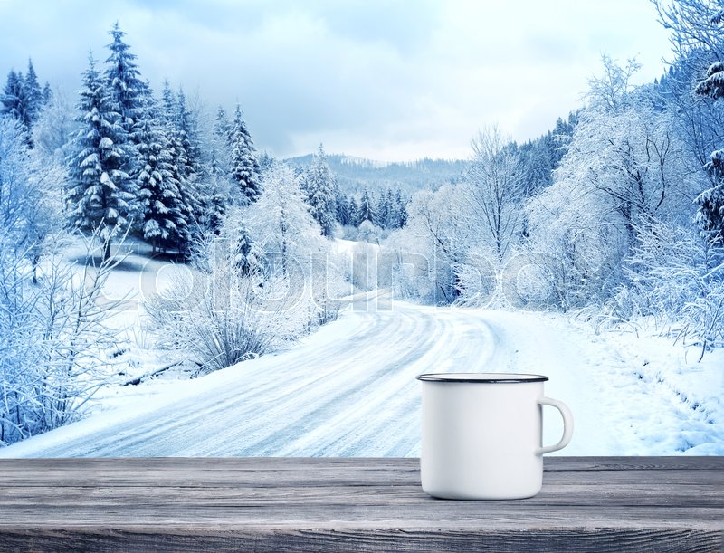 Stock image of 'White mug with drink on wooden table against background of winter landscape'