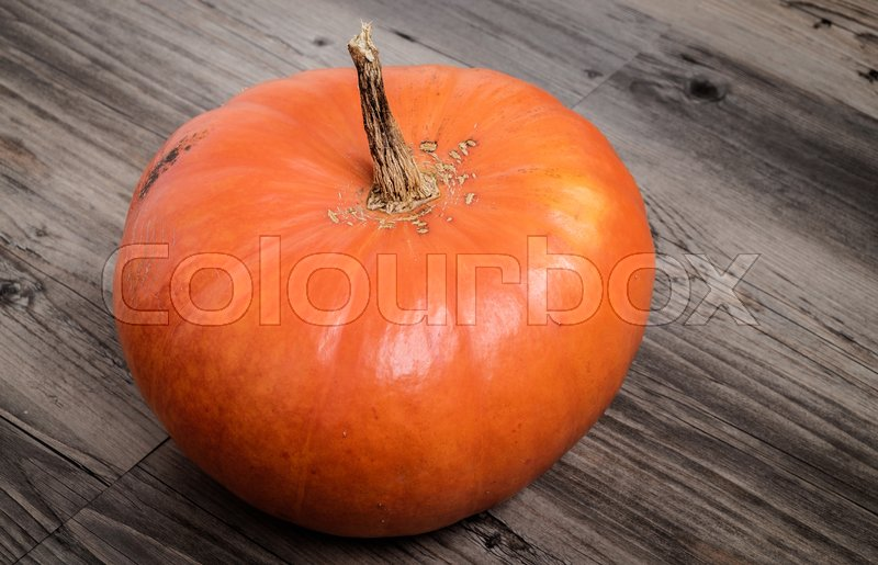 Stock image of 'Big pumpkin on table with wooden background'