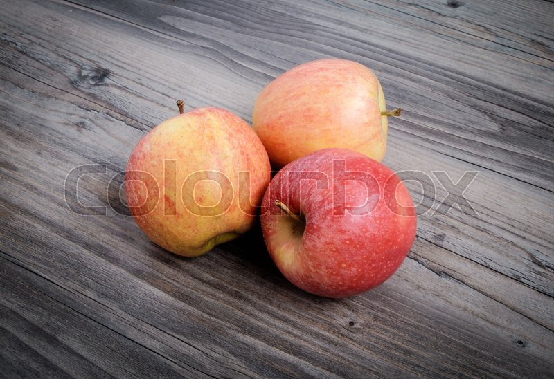 Stock image of 'Three fresh apples on table with wooden background'