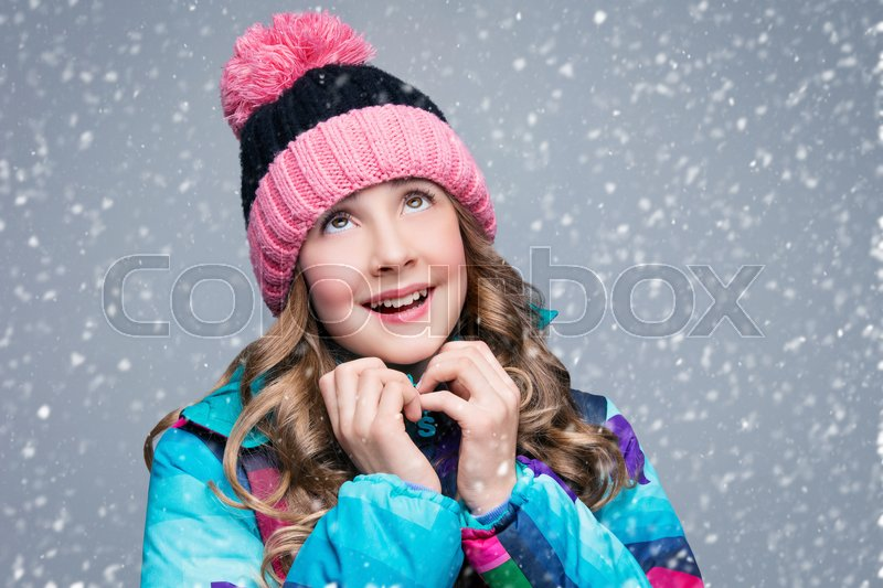 Stock image of 'Beautiful happy teen girl with long curly hair in pink wool hat and bright warm coat looking up. Studio shot over grey background with falling snow. Copy space.'
