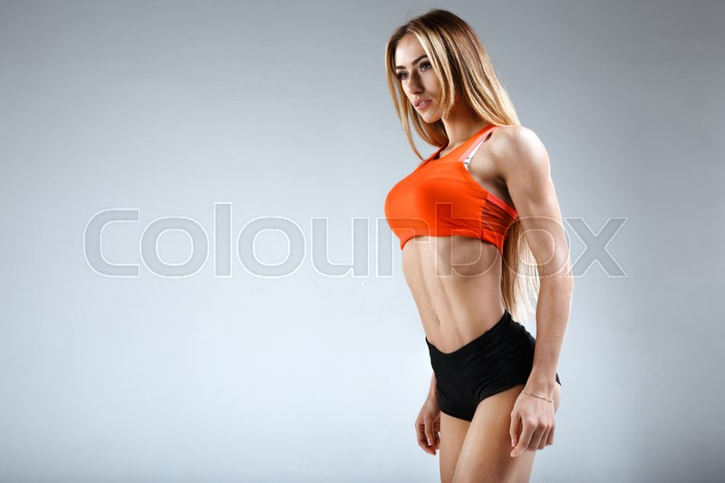 Stock image of 'Female slim fitness model in a perfect shape witn long hair and orange half-shirt is posing in the studio on the white background'