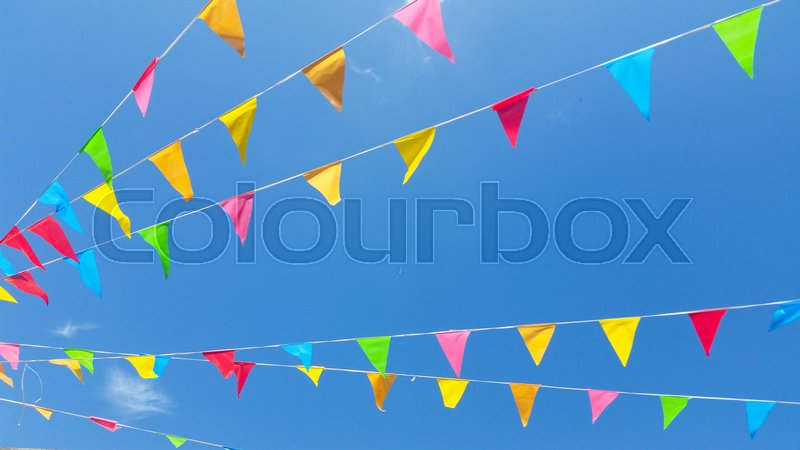 Stock image of 'row of colored flags flutter in the sky'