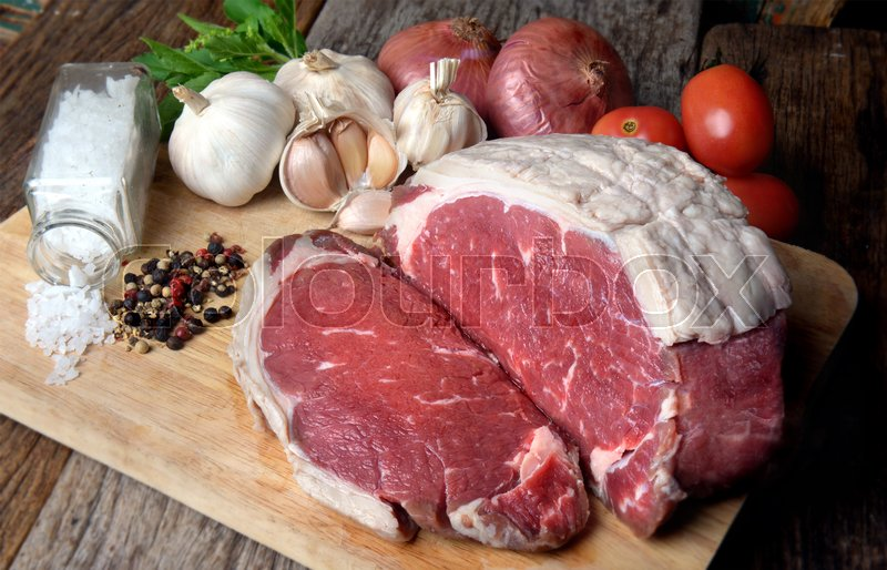 Stock image of 'Rare Angus beef cut and ready for cooking display with seasoning and vegetable ingredient photo in studio lighting.'