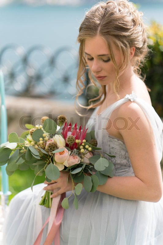 Stock image of 'beautiful young bride on a lawn poses for a photo on the wedding day'