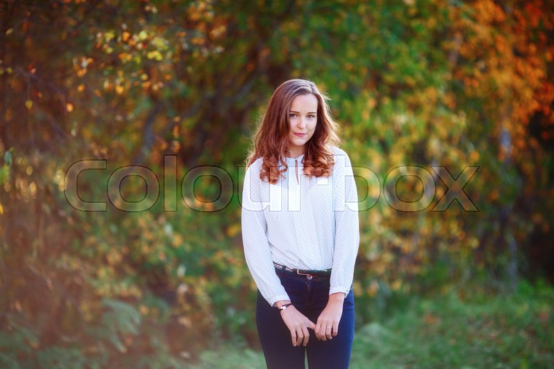 Stock image of 'Young woman. Smiling pretty girl posing in sunlight. Colorful autumn park'