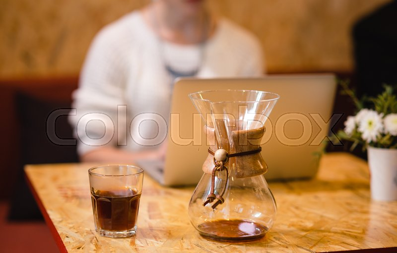 Stock image of 'Cropped shot view of young woman keyboarding on laptop computer with blank copy space screen while sitting in cafe, blonde female student working on net-book after her lectures in University,flare sun'