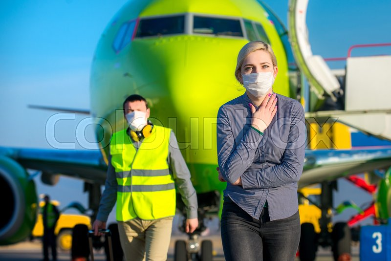 Stock image of 'Sick traveling tourist at an airport with mask on the face'