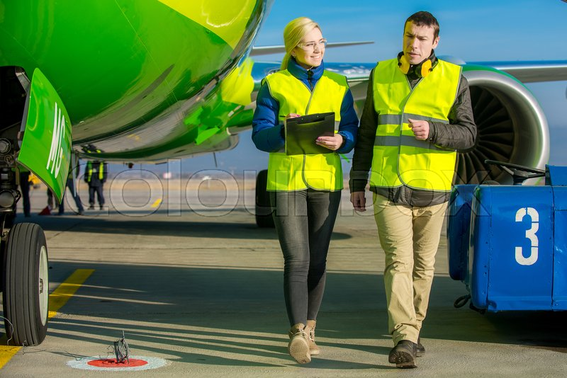 Stock image of 'airport staff workers preapre the airplane for flight'