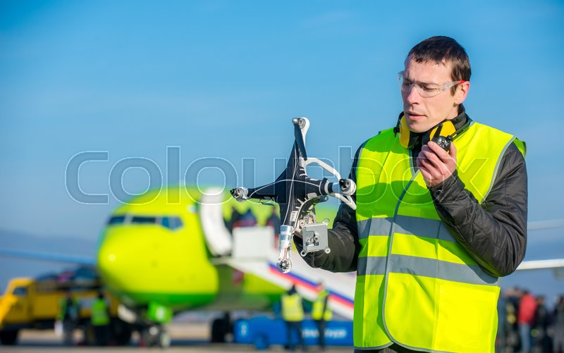 Stock image of 'airport worker holding crashed quadcopter near airliner'