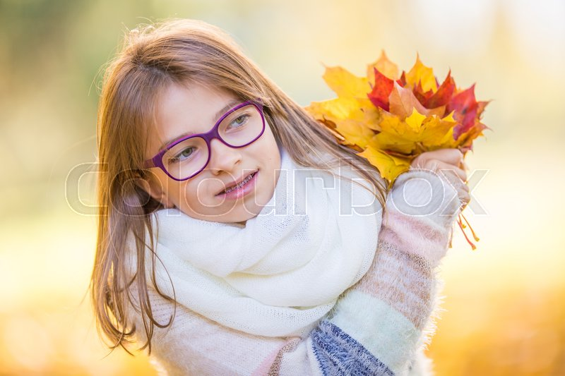 Stock image of 'Autumn. Portrait of a smiling young girl who is holding in her hand a bouquet of autumn maple leaves.Pre-teen young girl with glasses and teeth braces.'