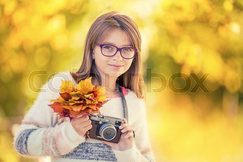 Stock image of 'Autumn time. The teenage attractive cute young girl with autumn bouquet and retro camera. Young girl photographer autumn  season.\'