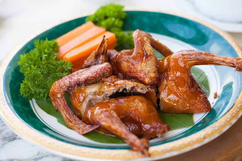 Stock image of 'A dish of Nice oily brown color of Fried pigeon put on a nice decorated plate in Cantonese restaurant in Vietnam'