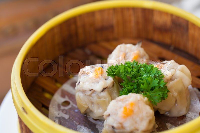 Stock image of 'Chinese steamed dumpling or Dim sum stuffed with minced pork decorated in bamboo made steamer local style.'