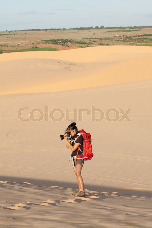 Stock image of 'Female photographer with her backpack travelling in windy white sand dunes at Muine desert, Phan thiet, Vietnam'