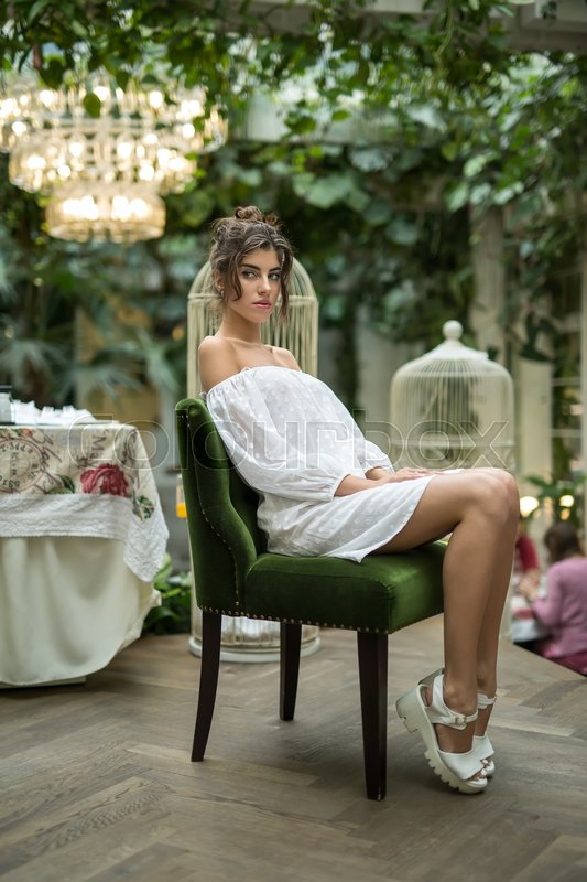 Stock image of 'Beautiful girl in a white dress and white sandals sits on the green chair in the restaurant with green plants and birdcages. Her legs are on the toes, hands are on the legs. She looks to the side.'