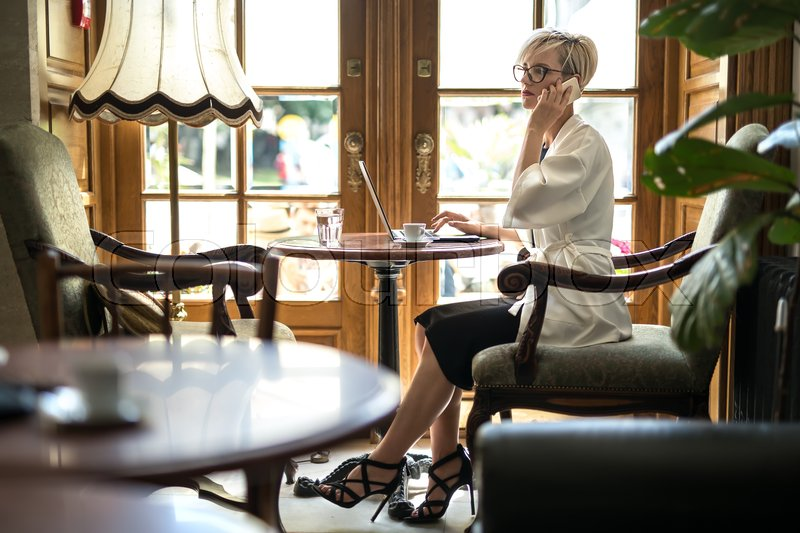 Stock image of 'Attractive blonde girl in glasses sits on armchair at the table in the restaurant and talks on the cell phone. Her right hand is on the laptop. Woman wears black dress and sandals, a white cloak.'