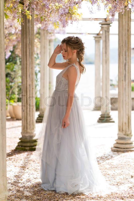 Stock image of 'young bride in a wedding dress poses on the terrace with columns'