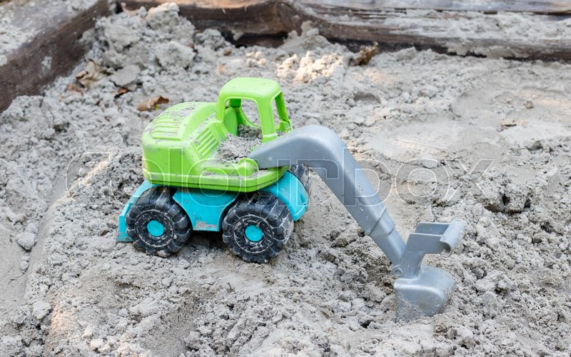 Stock image of 'Toy trucks on sand playground, industrail symbols'