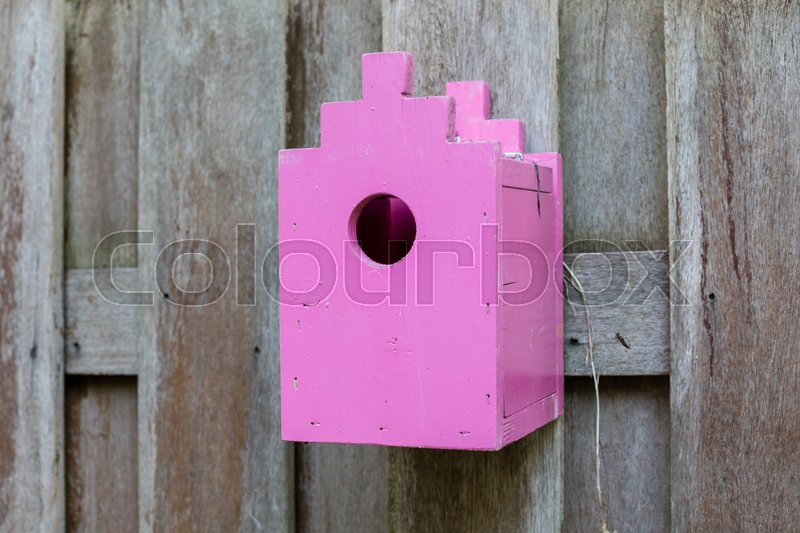 Stock image of 'Pink birdhouse on a wooden fence in a garden'