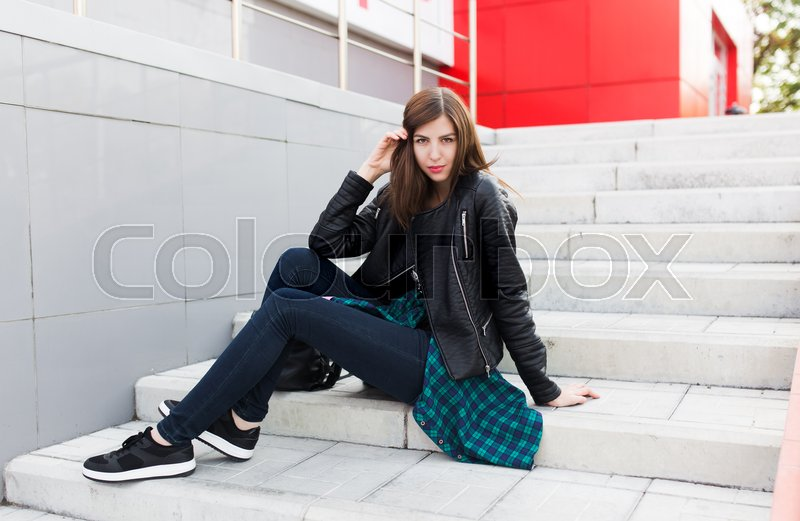 Stock image of 'Urban student girl posing in a leather jacket outdoors in the city.'
