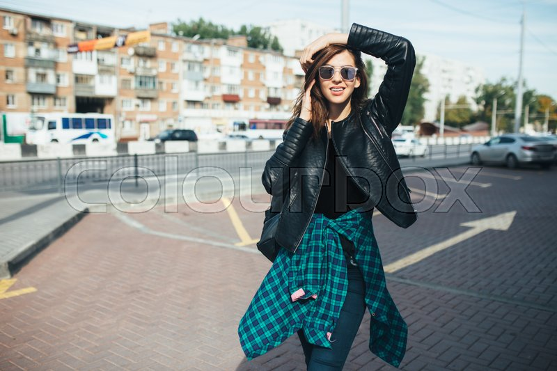 Stock image of 'Urban fashionable girl posing in a leather jacket outdoors in the city.'