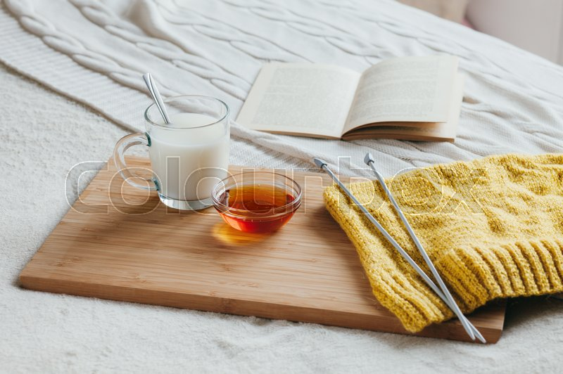 Stock image of 'Hot milk in a glass cup and honey on a wooden board. Treatment of hot drink. Treatment of folk remedies in bed. Knitting needles and yarn for knitting. The book to read.'