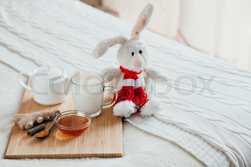 Stock image of 'Hot milk in a glass cup and honey on a wooden board. Treatment of children a hot drink. Treatment of folk remedies in bed. Soft toy bunny for your child.'