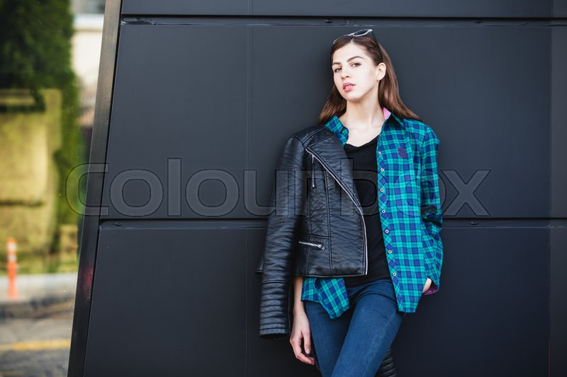 Stock image of 'Brunette girl in rock black style, wearing leather jacket standing outdoors in the city against the black urban wall.'