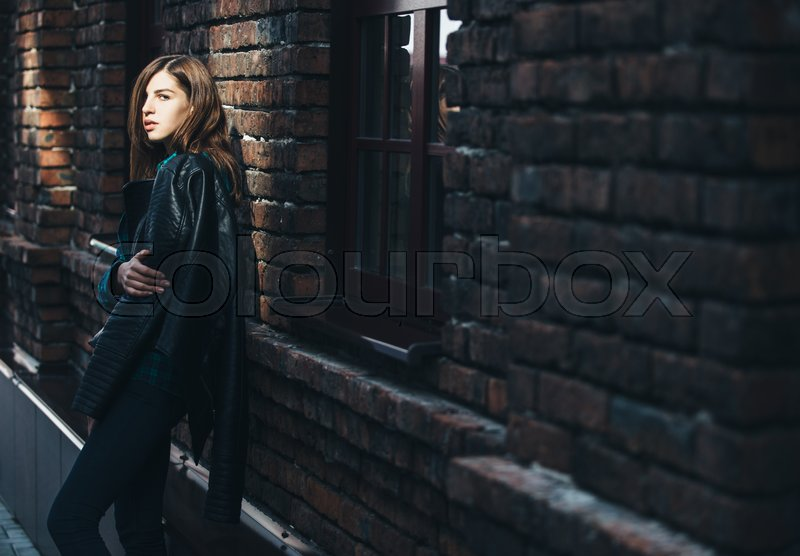 Stock image of 'Lifestyle fashion portrait of brunette girl in rock black style, standing outdoors in the city street.'