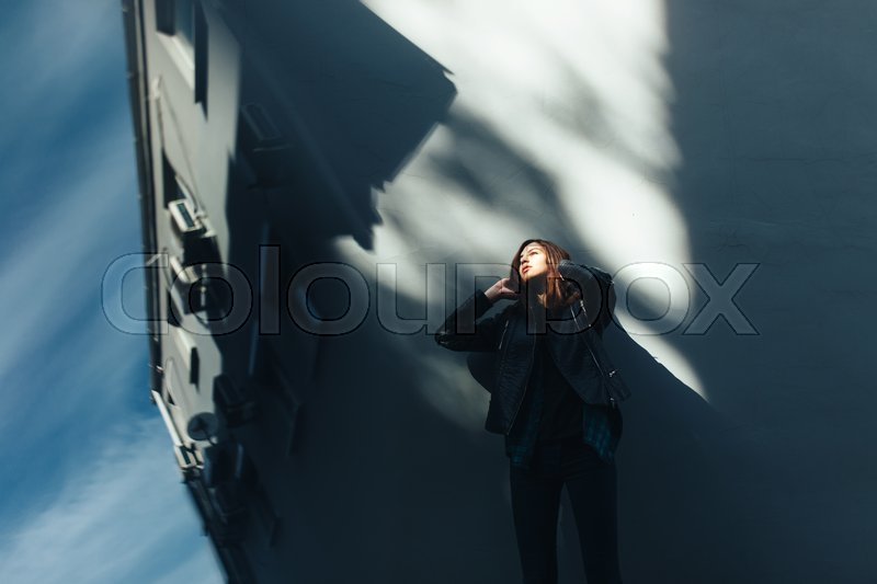 Stock image of 'Lifestyle fashion portrait of brunette girl in rock black style, standing outdoors in the city street'