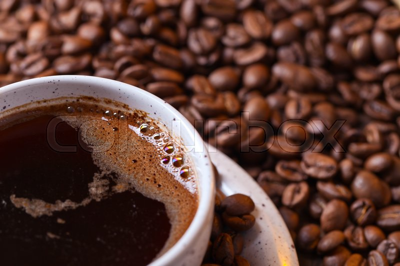 Stock image of 'Cup of black coffee and roasted beans'