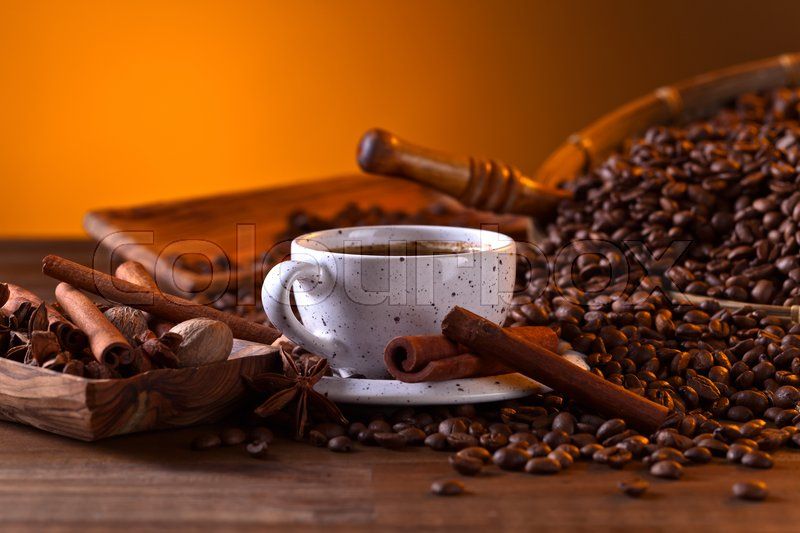 Stock image of 'Cup of black coffee and roasted beans with spices'