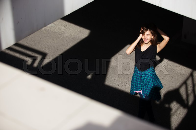 Stock image of 'Brunette girl in rock black style, standing outdoors in the city street'