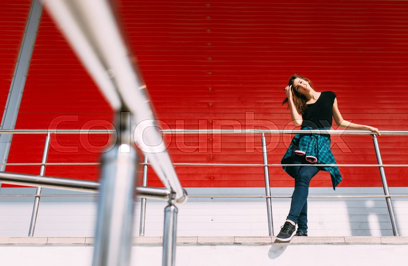 Stock image of 'Portrait of girl in rock black style, standing outdoors in the city against the red urban wall.'