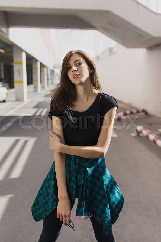 Stock image of 'Brunette girl in rock black style, standing outdoors in the city street.'