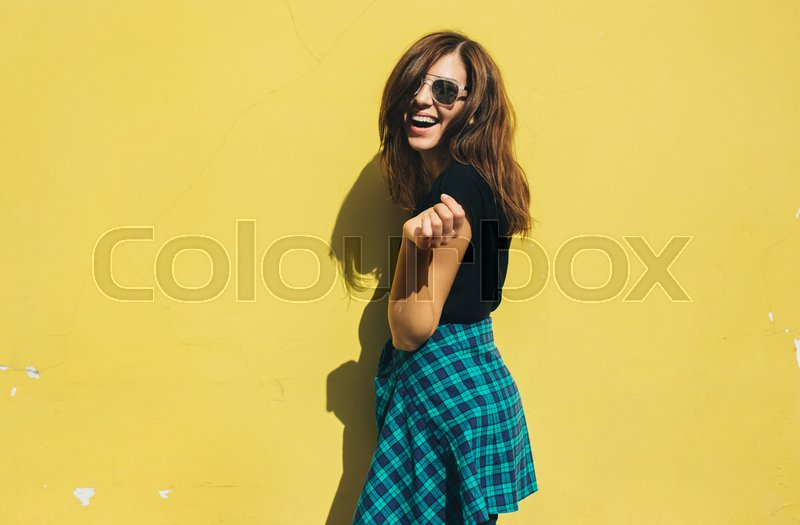Stock image of 'Brunette girl in rock black style, standing against yellow wall outdoors in the city street.'