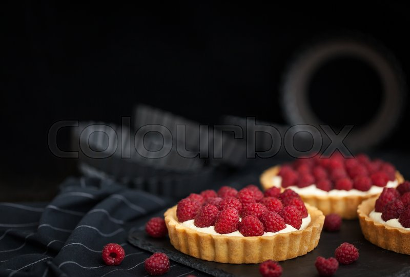 Stock image of 'Delicious raspberry mini tarts (tartlets) with whipped cream on dark background\'
