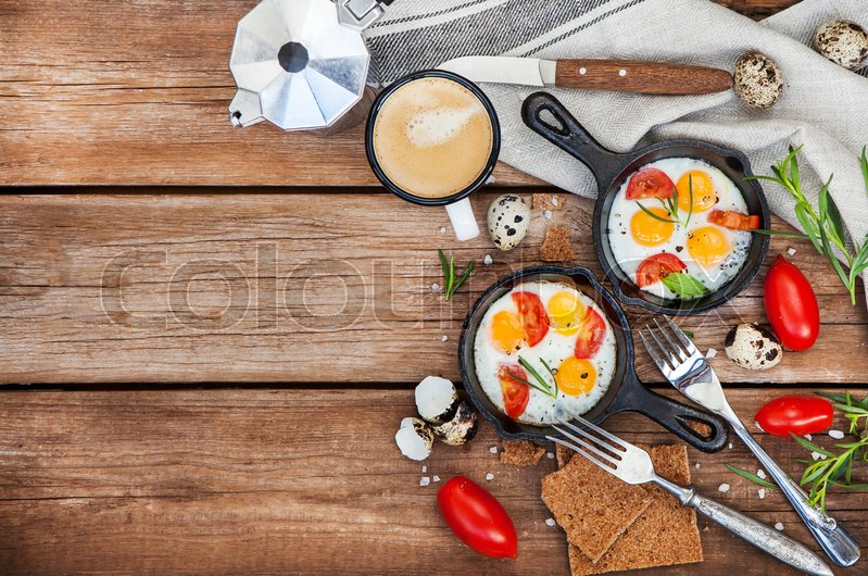 Stock image of 'Fried eggs with tomatoes in frying pans served for breakfast'