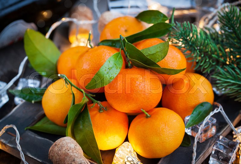 Stock image of 'Holiday concept: fresh tangerines, cork, glass, champagne, candles and garlands'
