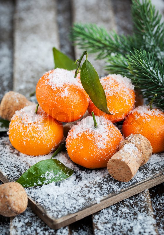 Stock image of 'Fresh tangerines with leaves on a snow-covered table with a branch of spruce'