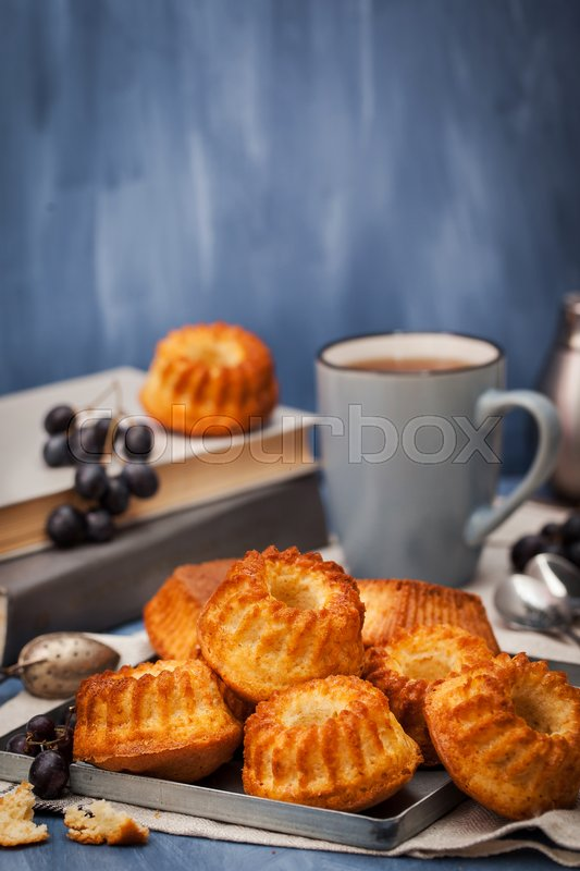 Stock image of 'Fresh homemade delicious mini bundt cakes (muffins) and cup of coffee on background'