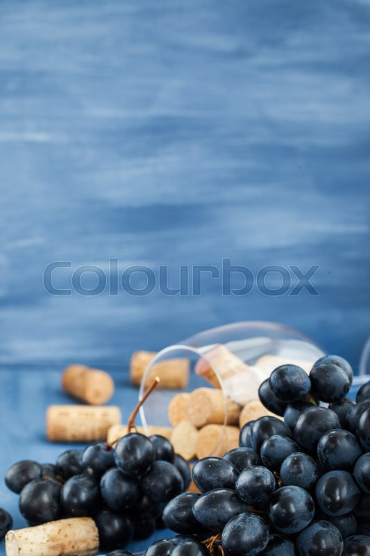 Stock image of 'Branch of purple grape and wine corks on the table with glass and bottle on background\'