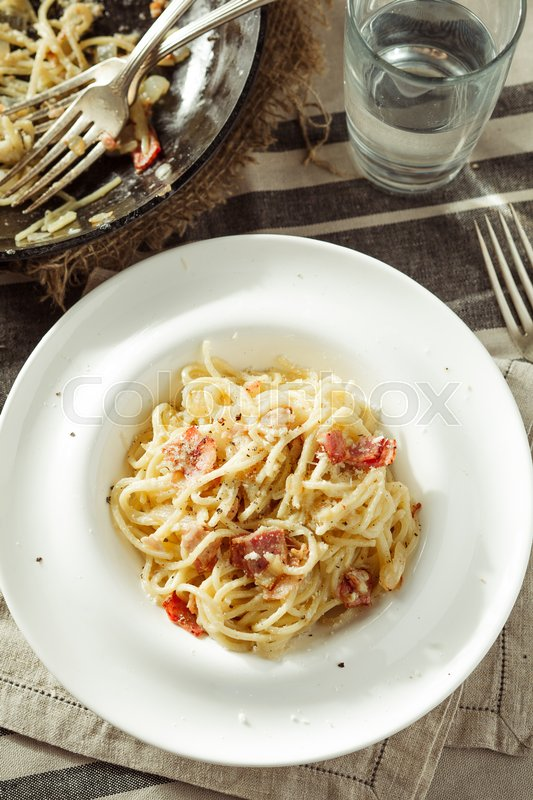 Stock image of 'Overhead view of plate of delicious spaghetti Carbonara. Rustic styled'