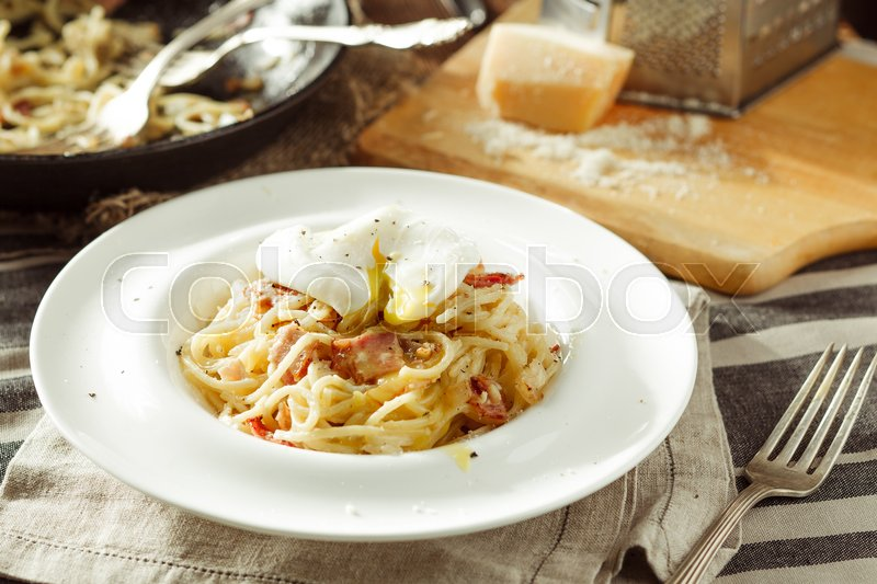Stock image of 'Plate of delicious spaghetti Carbonara with poached egg. Italian food. Rustic styled'