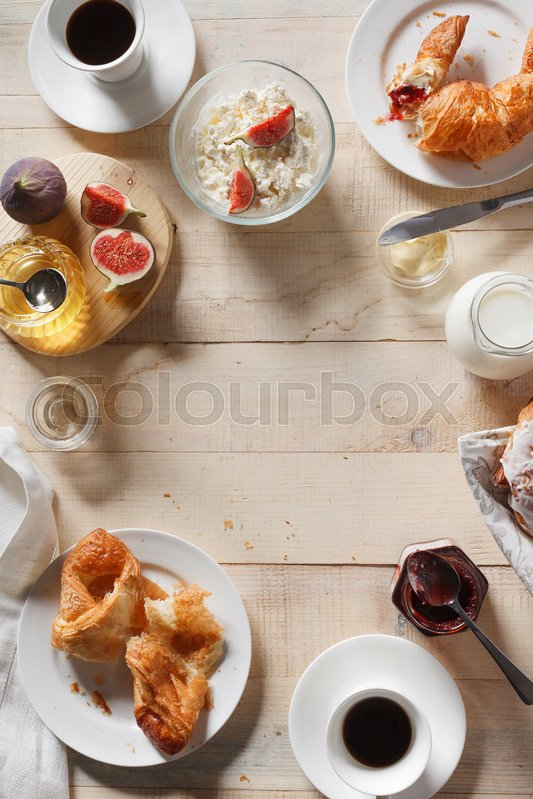 Stock image of 'Breakfast with croissants,  figs, curd, honey and espresso coffee on rustic serving board o, top view, copy space'