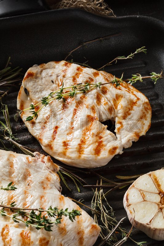 Stock image of 'Close-up view of fresh roasted chicken fillet on grill pan'